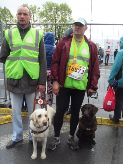 A photo capturing the moment after the finish with service dog association TEODORS Board Chairman Aleksejs Volkovs and Teodors