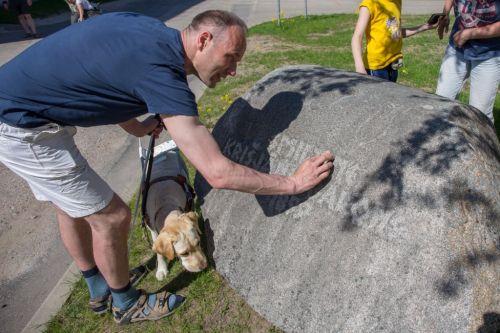 Aleksejs abserves / feels the memorial stone for Krišjānis Barons